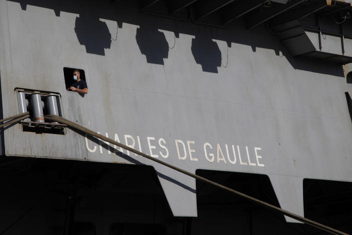 """A French crew member is seen of a window at France's nuclear-powered aircraft carrier Charles de Gaulle at Limassol port, Cyprus, Monday, May 10, 2021. With the Task Force's deployment on its mission named """"Clemenceau 21,"""" France is assisting in the fight against terrorism while projecting its military power in regions where it has vital interests. (AP Photo/Petros Karadjias)"""