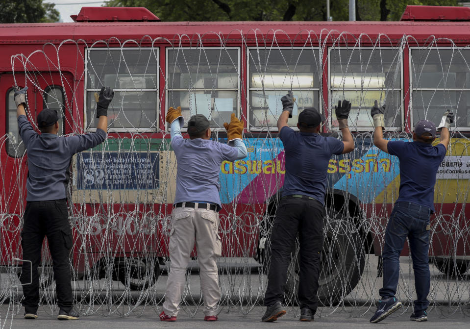 Men make barricades with buses, concreate blocks and barbed wires blocking a road heading to the Government House, office of the prime minister, ahead of a pro-democracy street march and a rally in Bangkok, Thailand Sunday, Nov. 8, 2020. (AP Photo/Rapeephat Sitichailapa)