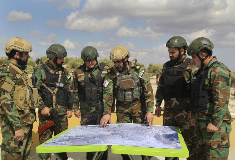 FILE - In this Monday Oct. 7, 2019 file photo, Turkish-backed forces from the Free Syrian Army look at a map during military maneuvers in preparation for a Turkish incursion targeting Syrian Kurdish fighters, near Azaz, north Syria. The Turkish trained and funded Syrian forces present themselves as heirs to the uprising against President Bashar Assad. But while they include some Islamist and former rebel factions, a large number are Arab and Turkmen fighters from northern and eastern Syria with an ax to grind against the Kurds and a reputation for violence and looting. (AP Photo, File)