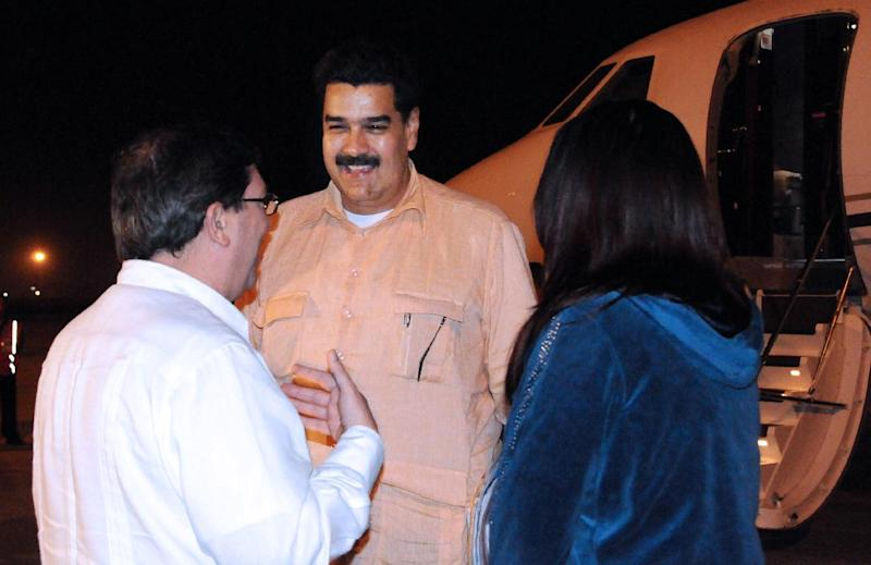 In this photo provided by Cuba's state newspaper Granma, Cuban Foreign Minister Bruno Rodriguez , left, talks with Venezuela's Vice President Nicolas Maduro, center, as Venezuelan Attorney General Cilia Flores watches at the Jose Marti International Airport in Havana on Saturday, Dec. 29, 2012. Maduro arrived in Cuba to visit Venezuelan President Hugo Chavez, who is recovering from a surgery_ his fourth operation related to his pelvic cancer since June 2011. (AP Photo/Granma, Juvenal Balan Neyra )