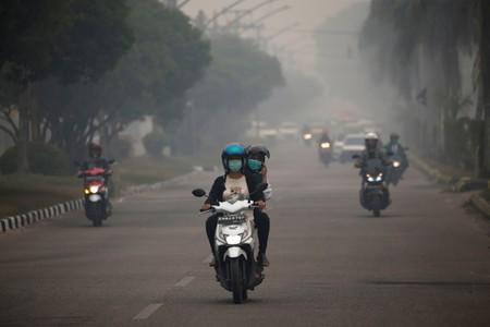 Motorists ride their motorbikes through haze due to a forest fire in Palangka Raya