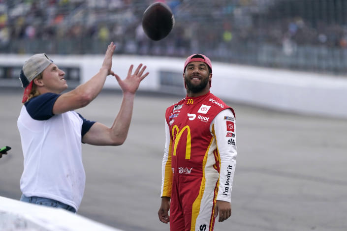 Bubba Wallace, right, smiles while watching New England Patriots wide receiver Gunner Olszewski catch a football thrown by a fan during a rain delay at the NASCAR Cup Series auto race Sunday, July 18, 2021, in Loudon, N.H. (AP Photo/Charles Krupa)