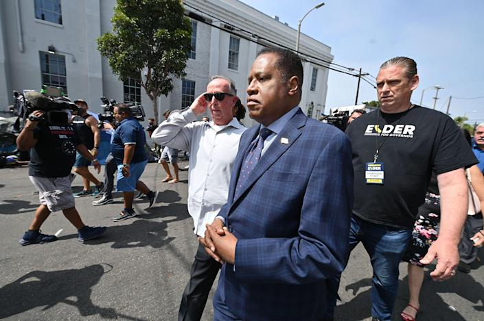 Conservative talk show host and gubernatorial recall candidate Larry Elder (C) walks along streets lined with tents of unhoused people, in the Venice neighborhood of  Los Angeles, California, 8 September 2021. (AFP via Getty Images)