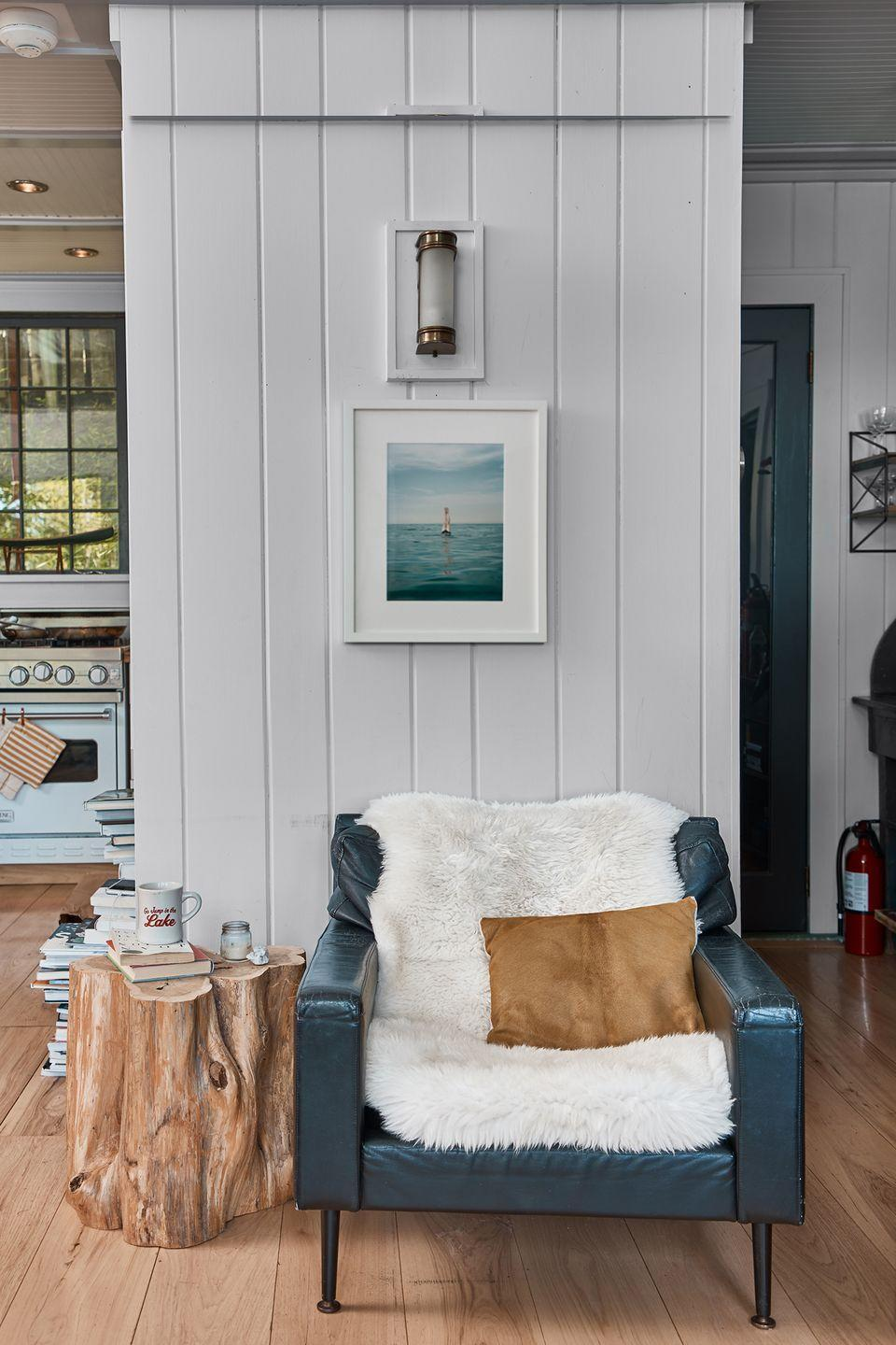 <p>The combination of shiplap walls and a tree stump end table boost this reading area's laid-back vibe. </p>