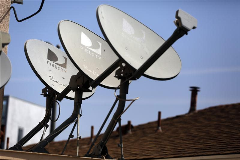 DirecTV satellite dishes are seen on an apartment roof in Los Angeles