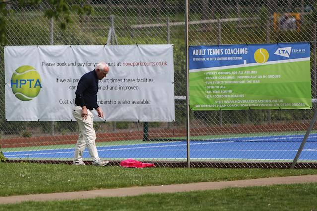 A man prepares for the reopening of tennis courts in Hove Park, near Brighton. (PA)