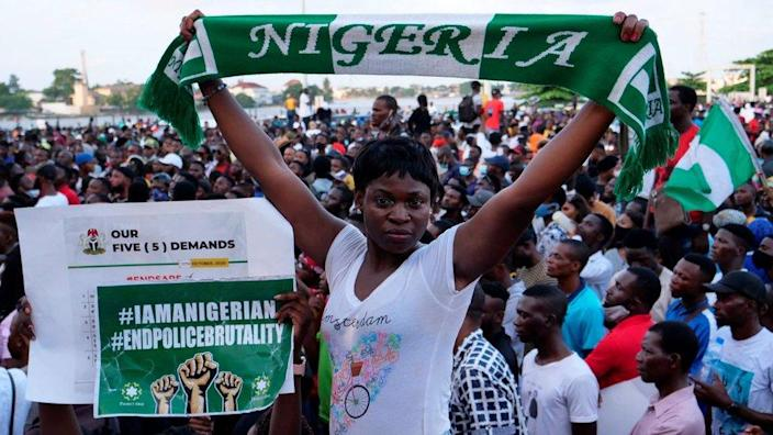 A protester holds up a scarf with the same colours as the Nigerian national flag during a live concert at the Lekki toll gate in Lagos, on October 15, 2020, during a demonstration to protest against police brutality and scrapping of Special Anti-Robbery Squad (SARS).