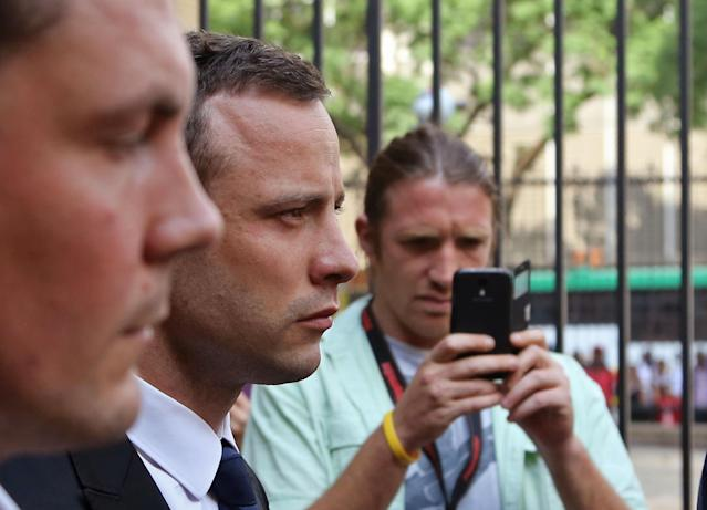Oscar Pistorius, second left, leaves the high court after the fourth day of his trial in Pretoria, South Africa, Thursday, March 6, 2014. Pistorius is charged with murder in the shooting death of girlfriend Reeva Steenkamp in the pre-dawn hours of Valentine's Day 2013. (AP Photo/Schalk van Zuydam)