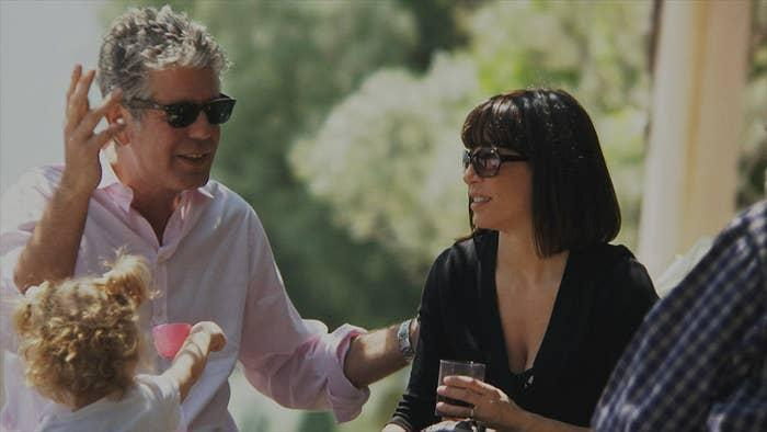Bourdain and Ottavia Busia sitting outdoors in the sun with family