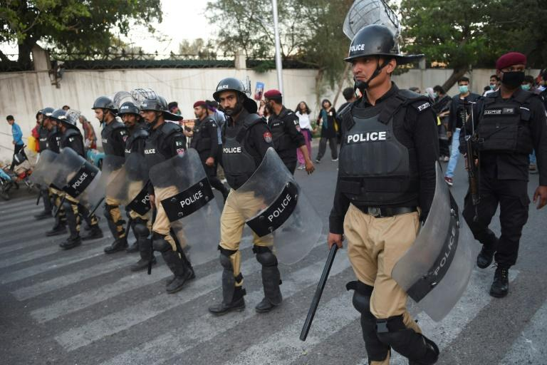 Pakistani riot police escort activists from the Aurat (Women) March in the southern port city of Karachi