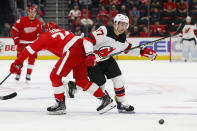 Detroit Red Wings defenseman Madison Bowey (74) checks New Jersey Devils left wing Kenny Agostino (17) off the puck during the first period of an NHL hockey game Friday, March 29, 2019, in Detroit. (AP Photo/Paul Sancya)
