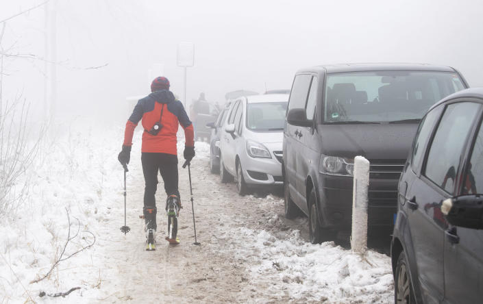 A cross-country skier passes illegally parked vehicles on highway 401 at Nienstedt, Germany, Tuesday, Jan. 5, 2020 Overcrowded parking spaces in snowy regions became a problem during the lockdown. (Julian Stratenschulte/dpa via AP)