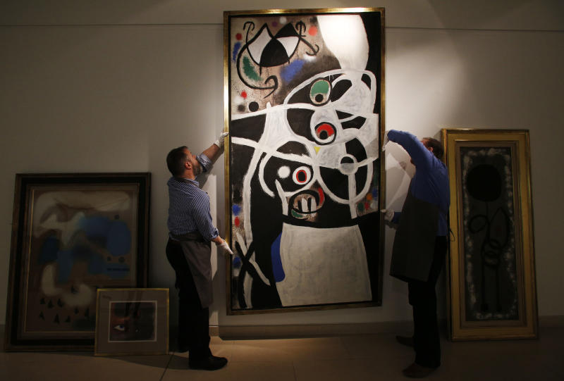 """In this Thursday, Dec. 19, 2013 photo, auction house workers adjust Joan Miro's 1968 oil painting """"Women and Birds"""" which has an estimated sale price of 4 to 7 million British pounds in a room with other works of Miro at Christie's auction house in central London. A trove of 85 works by the Spanish surrealist master that were acquired by the Portuguese government from a failing bank is up for auction with an estimated value of 30 million British pounds ($49 million). (AP Photo/Lefteris Pitarakis)"""
