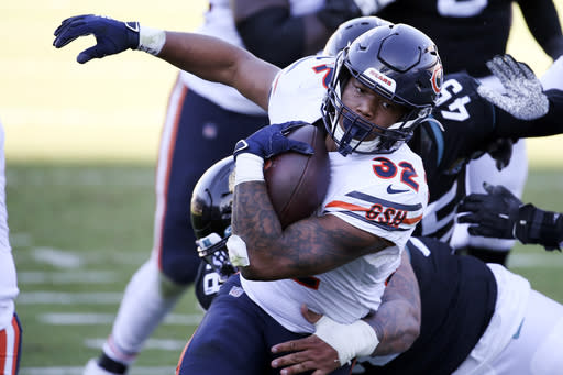 Chicago Bears running back David Montgomery (32) is stopped by Jacksonville Jaguars defensive tackle Doug Costin after a short gain during the second half of an NFL football game, Sunday, Dec. 27, 2020, in Jacksonville, Fla. (AP Photo/Stephen B. Morton)