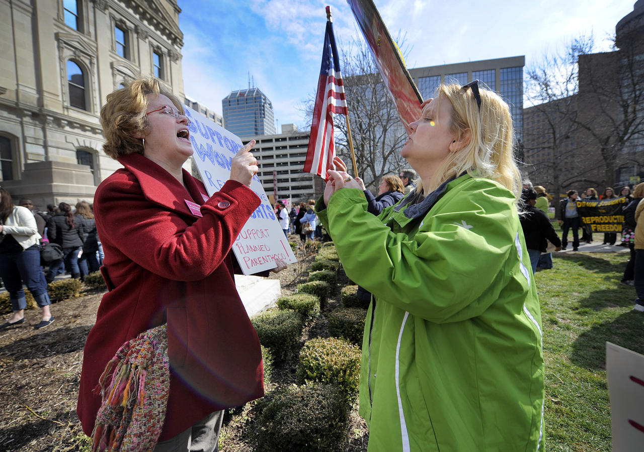 In this Tuesday, March 8, 2011 file photo, Planned Parenthood supporter Peg Paulson of Carmel, Ind., left, and opponent Heather Pruett of Indianapolis argue during a rally at the Indiana Statehouse on the South Lawn in Indianapolis in response to an Indiana House bill which would end funding to Planned Parenthood because it provides abortions. The nation's leading breast-cancer charity, Susan G. Komen for the Cure, is halting its partnerships with Planned Parenthood affiliates in 2012 - creating a bitter rift, linked to the abortion debate, between two iconic organizations that have assisted millions of women. Planned Parenthood says the cutoff, primarily affecting grants for breast exams, results from Komen bowing to pressure from anti-abortion activists. Komen says the key reason is that Planned Parenthood is under investigation in Congress - a probe launched by a conservative Republican who was urged to act by anti-abortion groups. (AP Photo/The Indianapolis Star, Alan Petersime)