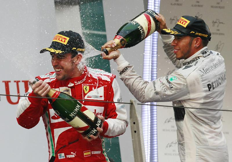 Ferrari driver Fernando Alonso, left, of Spain is sprayed with champagne by second placed Mercedes driver Lewis Hamilton of Britain after winning the Chinese Formula One Grand Prix in Shanghai, China, Sunday, April 14, 2013. (AP Photo/Eugene Hoshiko)