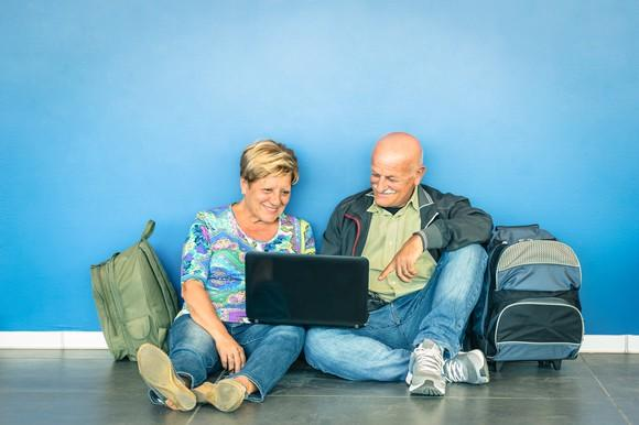 A senior couple sitting on the floor, looking at a laptop, with backpacks beside them.