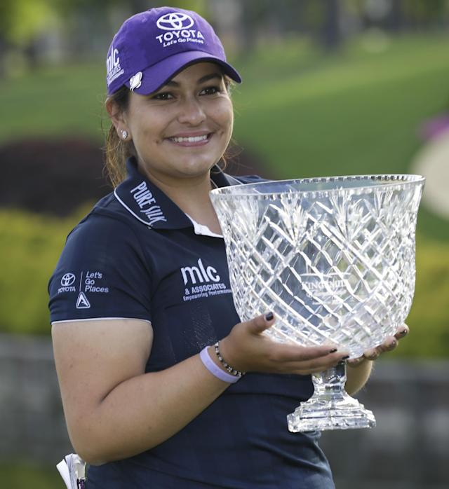 Lizette Salas holds the winners trophy as she celebrates winning the Kingsmill Championship golf tournament at the Kingsmill resort in Williamsburg, Va., Sunday, May 18, 2014. Salas won her first LPGA event after shooting an even par-71 leaving her at 13-under for the tournament. (AP Photo/Steve Helber)