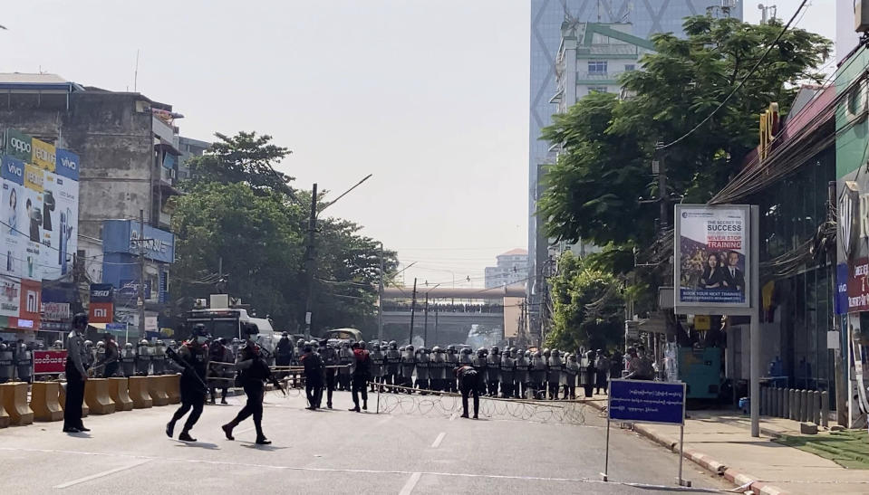 In this image made from video, a row of riot police blocks the road to prevent protesters from marching forward Saturday, Feb. 6, 2021 in Yangon, Myanmar. Myanmar's new military authorities appeared to have cut most access to the Internet on Saturday as they faced a rising tide of protest over their coup that toppled Aung San Suu Kyi's elected civilian government.(AP Photo)