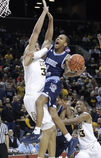 Rhode Island's Fatts Russell, right, drives against VCU's Marcus Santos-Silva, left, during the second half of an NCAA college basketball game in the Atlantic 10 men's tournament Friday, March 15, 2019, in New York. Rhode Island won 75-70. (AP Photo/Frank Franklin II)