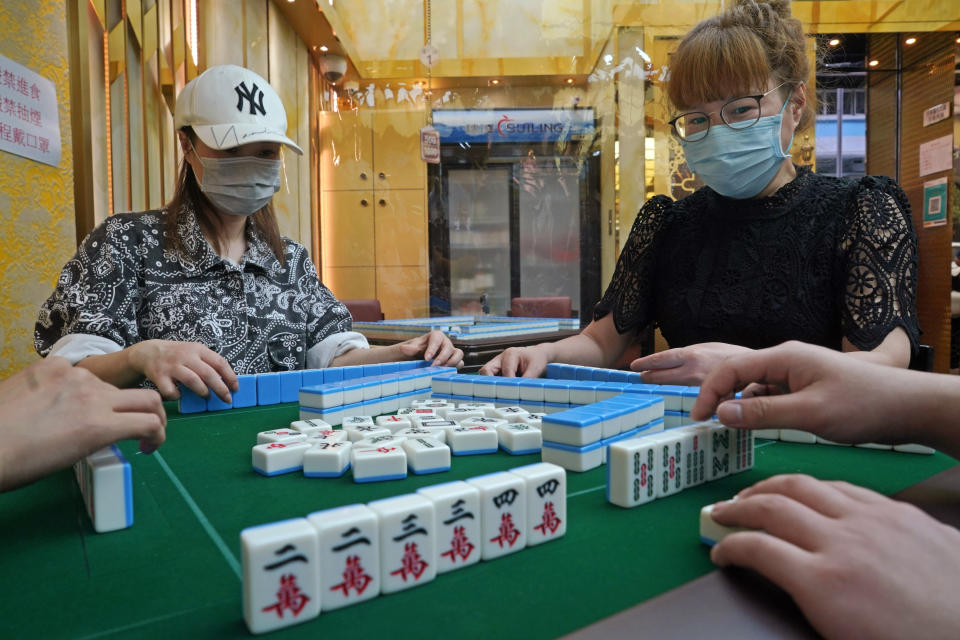 """Staff members wearing protective masks demonstrate their safety measures to the media at a mahjong parlor in Hong Kong, Wednesday, April 28, 2021, to comply with the """" Vaccine Bubble"""" requirements by the government to resume their business. Hong Kong health officials announced that they will relax COVID-19 social distancing measures starting on Thursday. It will include reopening bars and nightclubs, extending dining hours and allowing more diners per table, under the circumstances that customers and venue staff have been vaccinated. (AP Photo/Kin Cheung)"""