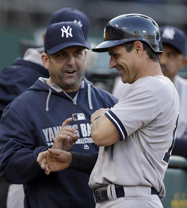 New York Yankees' Brian Roberts, right, is congratulated by hitting coach Kevin Long after scoring against the Oakland Athletics in the second inning of a baseball game on Friday, June 13, 2014, in Oakland, Calif. Roberts scored on a single by Brett Gardner. (AP Photo/Ben Margot)