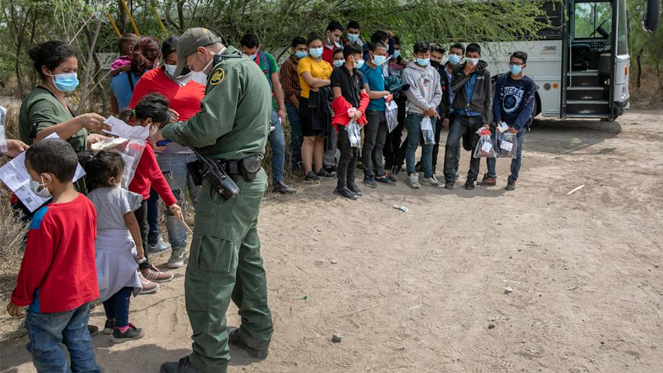 A U.S. Border Patrol agents questions families, as a group of unaccompanied minors (R), looks on after they crossed the Rio Grande into Texas on March 25, 2021 in Hidalgo, Texas. (John Moore/Getty Images)