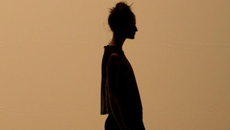 A side-profile silhouette of a woman