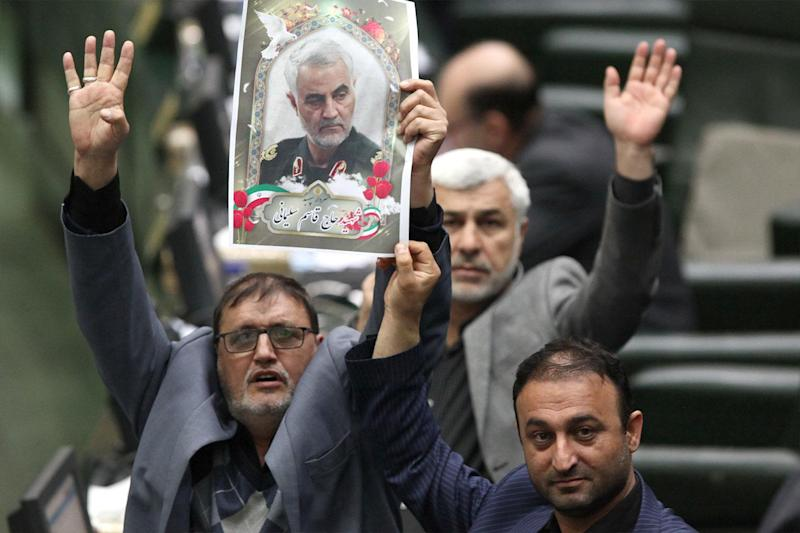 "Iranian lawmakers holding pictures of slain top general Qasem Soleimani as they vote during a parliamentary session in Tehran on Jan. 7, 2020. - Iran's parliament passed a bill designating all US forces ""terrorists"" over the killing of a top Iranian military commander in a US strike last week. Under the newly adopted bill, all US forces and employees of the Pentagon and affiliated organizations, agents and commanders and those who ordered the ""martyrdom"" of Soleimani were designated as ""terrorists"". (Photo: /ICANA NEWS AGENCY /AFP via Getty Images)"