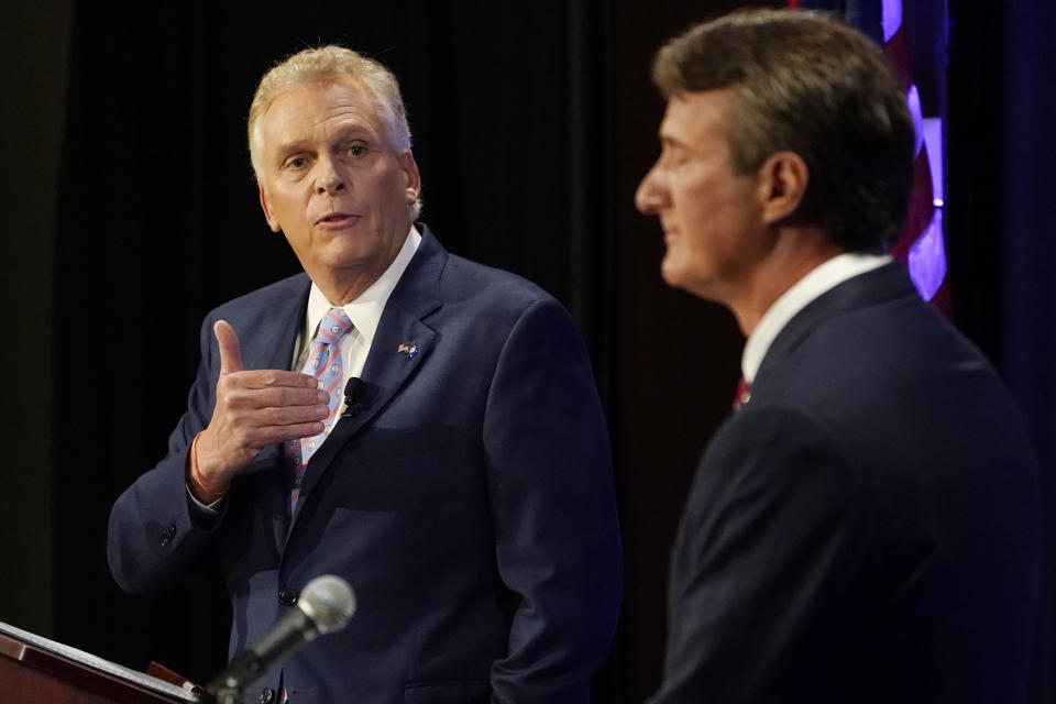 Terry McAuliffe gestures as Glenn Youngkin listens during a debate.