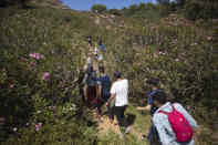 People cross a forest in the border town of Fnideq in northern Morocco on their way to the Spanish enclave of Ceuta, Tuesday, May 18, 2021. (AP Photo/Mosa'ab Elshamy)