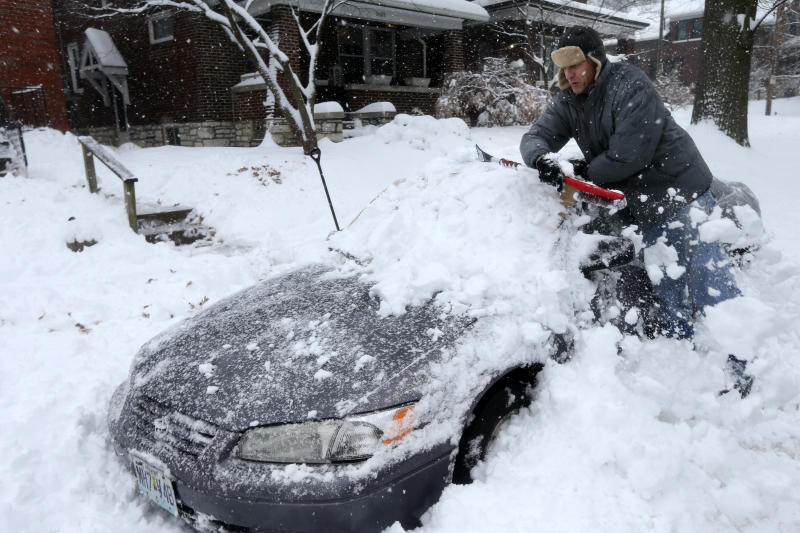 Jeff Clifford digs out his girlfriend's car from a pile of snow on Saturday, Jan. 12, 2019, in St. Louis. A winter storm swept the region this weekend, snarling traffic in several states and leaving thousands without power. (Laurie Skrivan/St. Louis Post-Dispatch via AP)