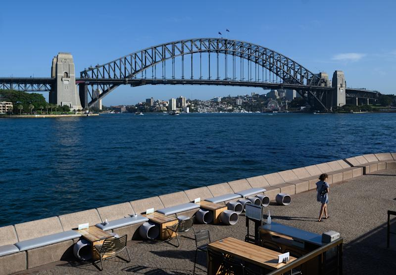 A lone woman walks through a quiet Opera Bar in front of the Sydney Harbour Bridge. Source: AAP