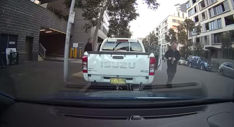 Two City of Sydney parking inspectors exit a ute after backing into a car parked behind it. The owner of the car claims the men didn't leave a note.