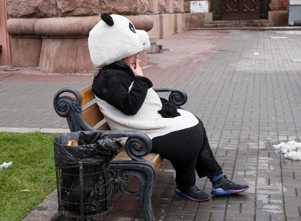 A man dressed as a panda rests and smokes in between posing for pictures with tourists in central Kiev, Ukraine December 13, 2017. REUTERS/Gleb Garanich     TPX IMAGES OF THE DAY