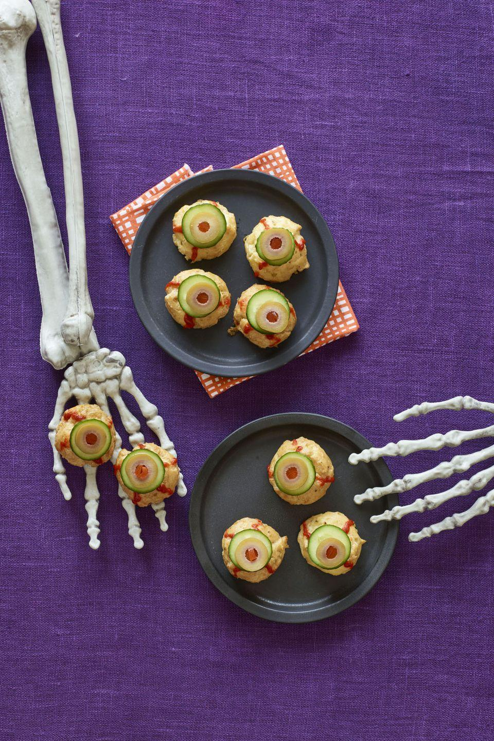 "<p>Top these cheese pastry puffs with slices of cucumber, olives, and squiggles of spicy Sriracha for a Halloween treat you won't be able to take your eyes off.</p><p><strong><a href=""https://www.womansday.com/food-recipes/recipes/a60165/bitesize-eyeballs-recipe/"" rel=""nofollow noopener"" target=""_blank"" data-ylk=""slk:Get the recipe"" class=""link rapid-noclick-resp"">Get the recipe</a>.</strong></p>"