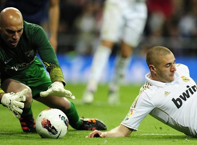 Real Madrid's French forward Karim Benzema (R) vies with Malaga's Argentinian goalkeeper Willy Caballero (L) during the Spanish league football match Real Madrid vs Malaga at the Santiago Barnabeu stadium in Madrid on March 18, 2012. (Photo by Javier Soriano/AFP/Getty Images)