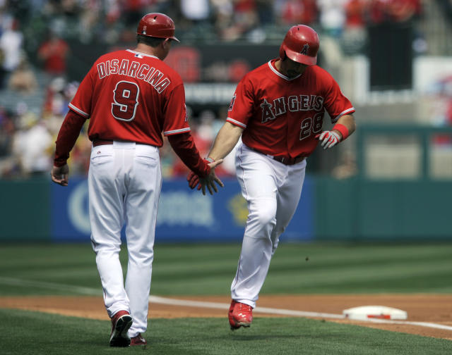 Los Angeles Angels' Raul Ibanez, right, celebrates with third base coach Gary DiSarcina as he rounds third base after hitting a one-run home run off New York Mets starting pitcher Bartolo Colon during the first inning of a baseball game in Anaheim, Calif., Sunday, April 13, 2014. (AP Photo/Kelvin Kuo)