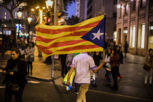 A man with an independence flag walks through downtown Barcelona on Oct. 28. (Photo: Santi Palacios/AP)
