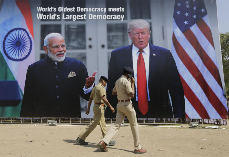 Indian policemen walks past a hoarding welcoming U.S President Donald Trump, at the airport ahead of his visit in Ahmedabad, India, Saturday, Feb. 22, 2020. To welcome Trump, who last year likened Modi to Elvis Presley for his crowd-pulling power at a joint rally the two leaders held in Houston, the Gujarat government has spent almost $14 million on ads blanketing the city that show them holding up their hands, flanked by the Indian and U.S. flags. (AP Photo/Ajit Solanki)