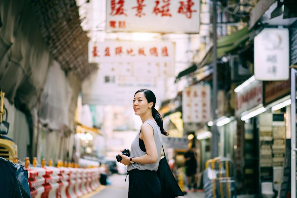A woman carrying a camera, exploring and walking through local city street. (PHOTO: Getty Images)