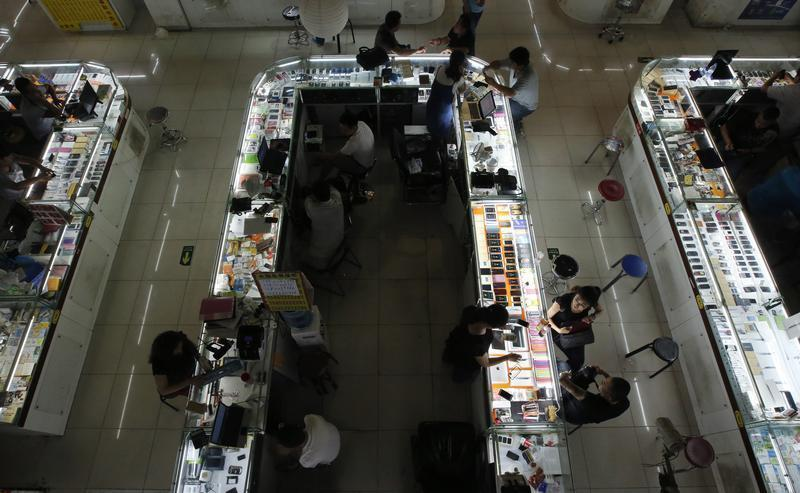 Sales people negotiate with customers at booths selling mobile phones at a shopping mall in Beijing