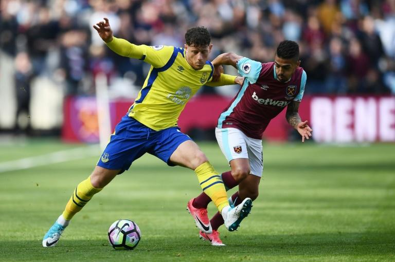 Everton's Ross Barkley (L) fights for the ball with West Ham United's Manuel Lanzini during their English Premier League match, at The London Stadium, on April 22, 2017