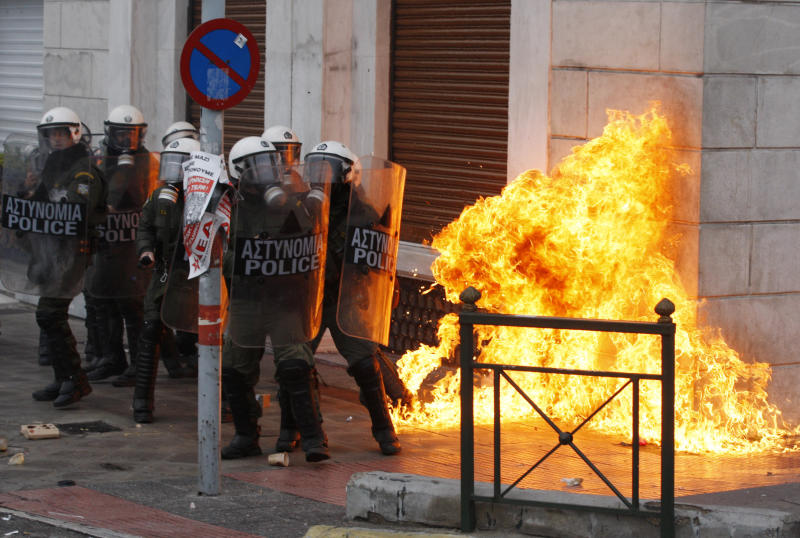 Riot police try to avoid a petrol bomb outside a luxury hotel during clashes in Athens, Wednesday, Dec. 15, 2010. Hundreds of protesters clashed with riot police across central Athens Wednesday, smashing cars and hurling gasoline bombs during a massive labor protest against the government's austerity measures. Wednesday's violence occurred after some 20,000 protesters marched to parliament during a general strike against a new round of labor reforms in the crisis-hit country. (AP Photo/Thanassis Stavrakis)