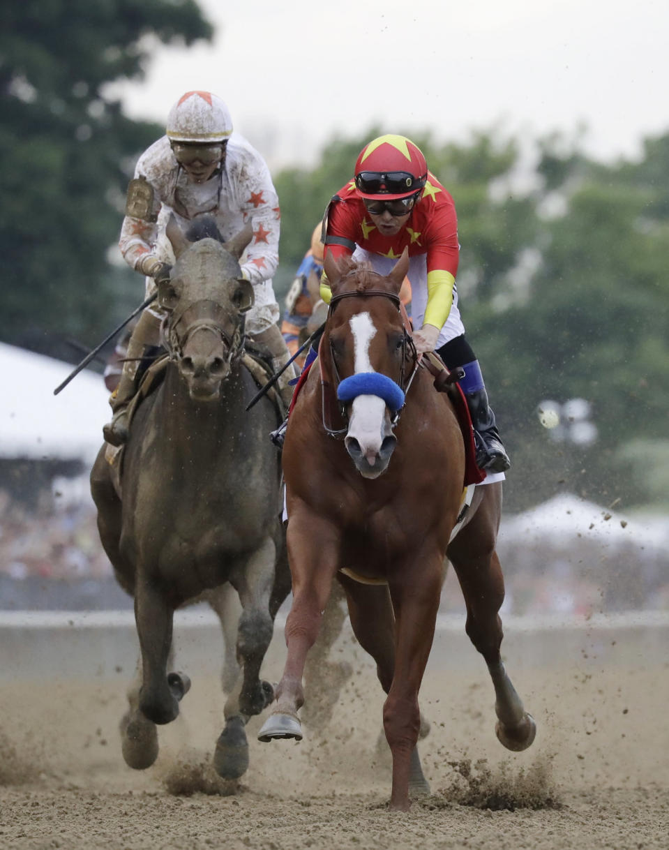 Justify (1), with jockey Mike Smith up, right, crosses the finish line ahead of Gronkowski, right, with jockey Jose Ortiz up, to win the 150th running of the Belmont Stakes horse race and the Triple Crown, Saturday, June 9, 2018, in Elmont, N.Y. (AP Photo/Julio Cortez)
