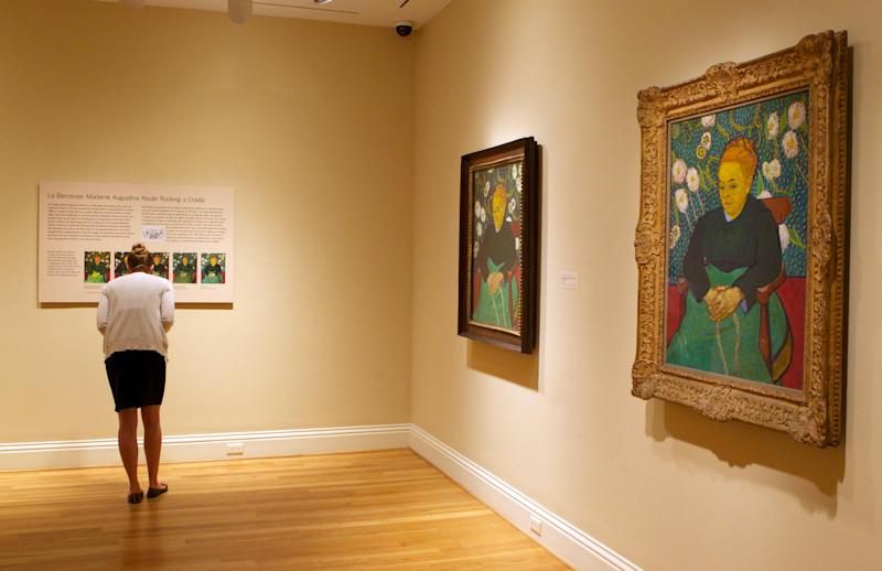 "In this Oct. 8, 2013 photo, a woman reads about Vincent van Gogh's repetition of ""Madame Roulin Rocking the Cradle,"" right, on display at The Phillips Collection in Washington. In the midst of the shutdown of federally funded museums, the private Phillips Collection is launching the first major exhibition of Vincent van Gogh's artwork in Washington in 15 years. (AP Photo/Molly Riley)"