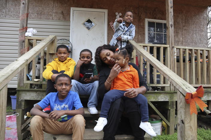 """Annie Turner sits with five of her six children, from top left, Kendell Turner Jr., 10; Keydon Turner, 6; Kendrell Turner, 9; Kemiya Turner, 2, and Kejuan Turner, 8, in front of their home in Fayette, Miss., on Monday, March 22, 2021. She said receiving food from the school helps supplement what she is able to provide. It's tough being the family's breadwinner during a pandemic. """"It's really put a strain on me — big time."""" (AP Photo/Leah Willingham)"""