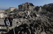 Men look at the ruins of a house following recent shelling during a military conflict over the breakaway region of Nagorno-Karabakh, in Stepanakert