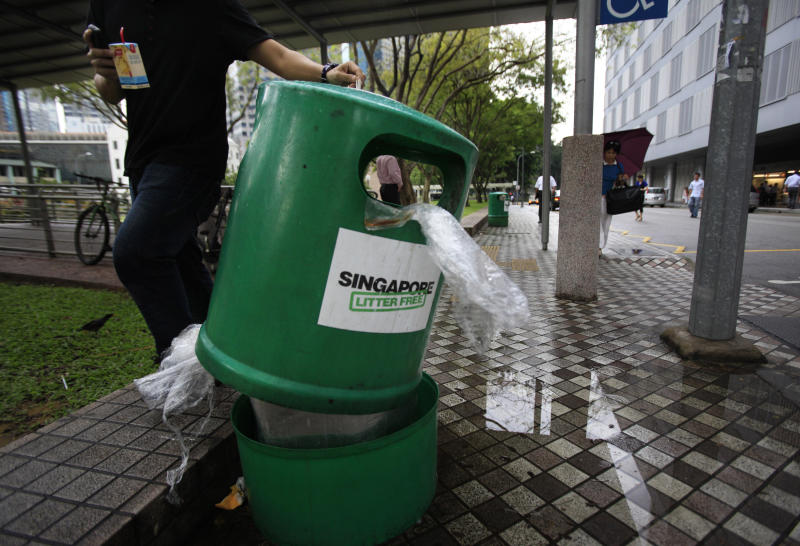 "A man stubs out his cigarette on a trash bin bearing ""Singapore Litter Free"" sticker on Monday, June 7, 2010 in Singapore. Singapore, where painting graffiti can get you caned and drug smugglers are hanged, is trying a new tactic against the city-state's litterbugs: Embarrassing them in front of their neighbors. (AP Photo/Wong Maye-E)"