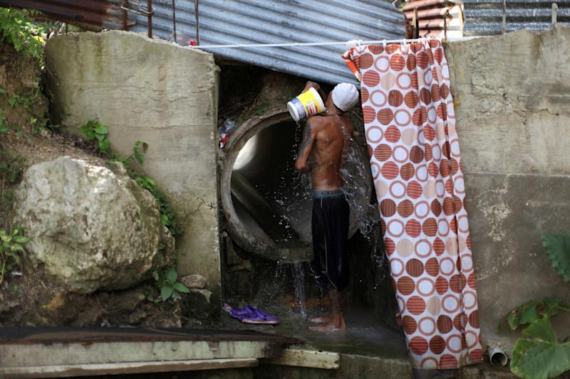 Israel Ayala takes a bath with water coming through a pipe on Oct. 19, 2017, after Puerto Rico was hit by Hurricane Maria in September. (Alvin Baez / Reuters)